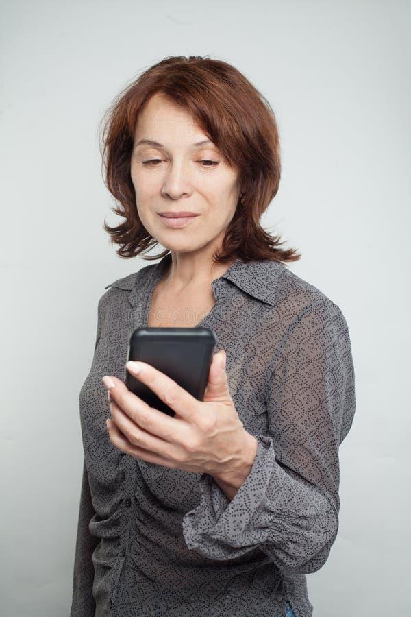 Mulher madura com telefone celular móvel foto de stock royalty free