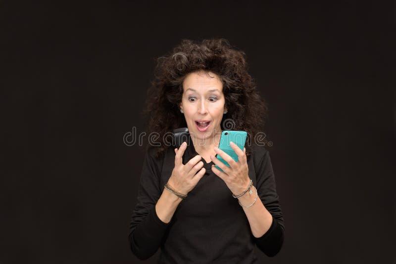 A mulher madura com telefones de 2 células surpreendeu a boca aberta imagem de stock royalty free