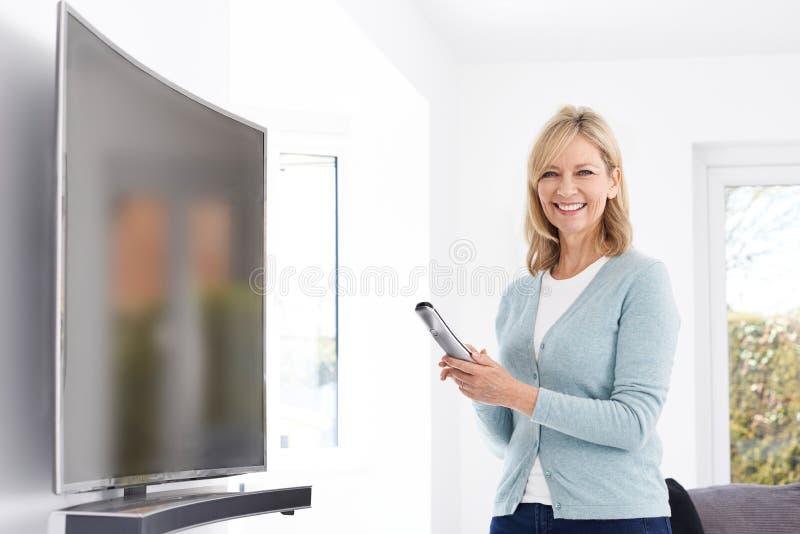 Mulher madura com a televisão curvada nova da tela em casa fotografia de stock