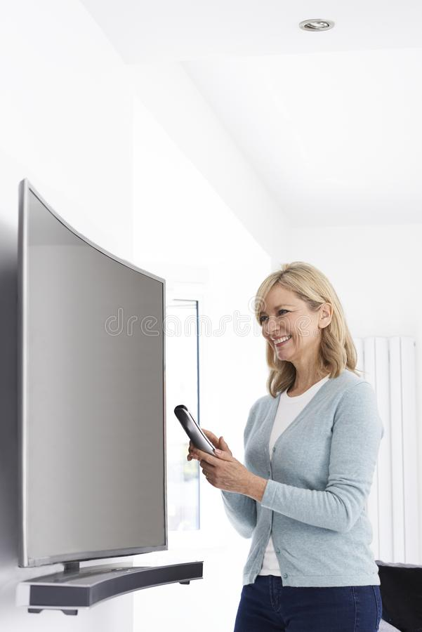 Mulher madura com a televisão curvada nova da tela em casa fotos de stock royalty free