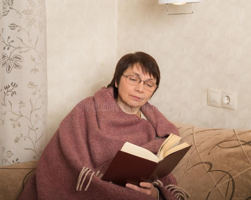 Mulher madura com um livro imagens de stock royalty free
