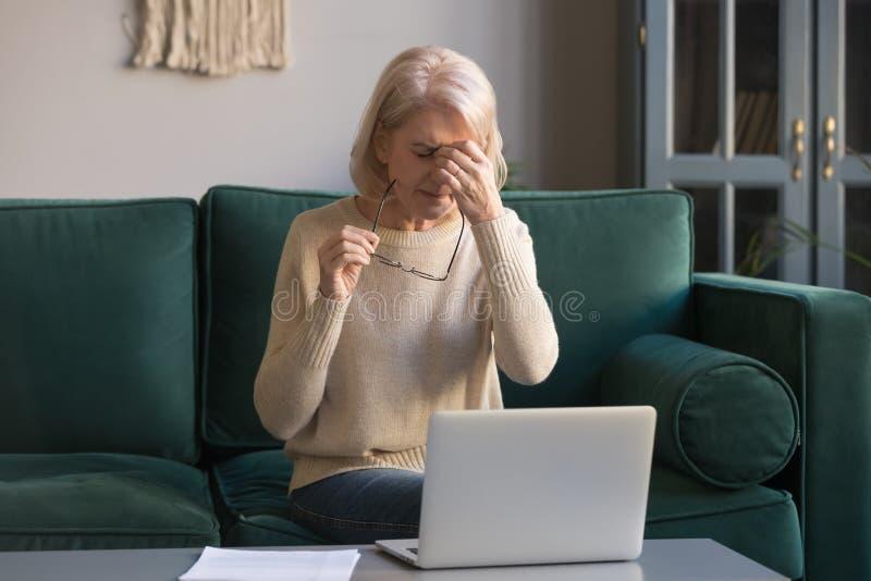 Mulher madura de cabelo cinzenta que faz massagens a ponte do nariz, conceito da fadiga ocular imagem de stock royalty free