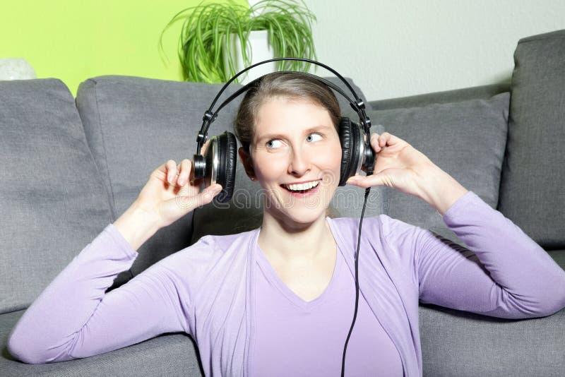 Mulher madura de riso que escuta a música fotografia de stock