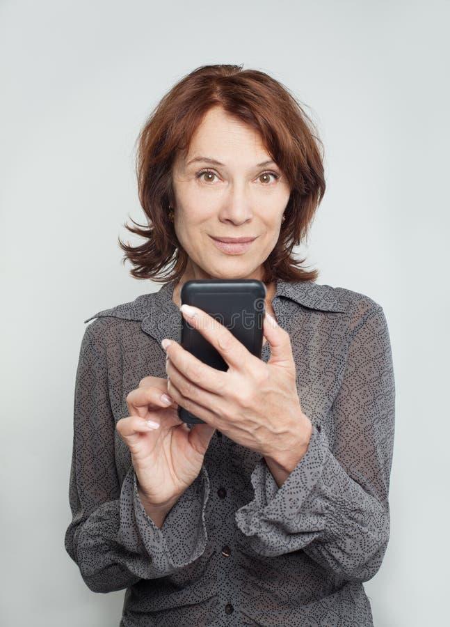 Mulher madura de sorriso com telefone celular imagem de stock royalty free