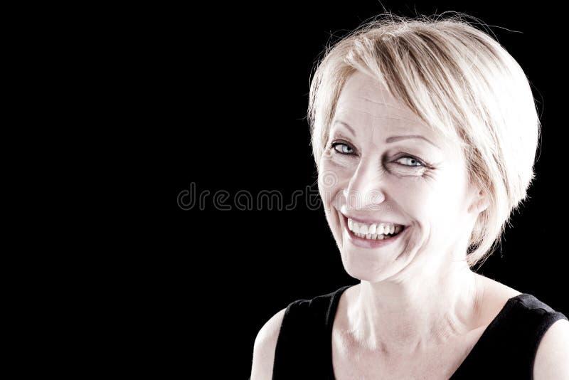Mulher madura de sorriso no preto fotos de stock