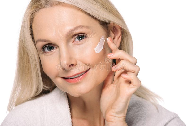 mulher madura de sorriso que aplica o creme cosmético imagem de stock royalty free