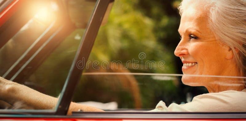 Mulher madura de sorriso que conduz o convertible vermelho imagens de stock