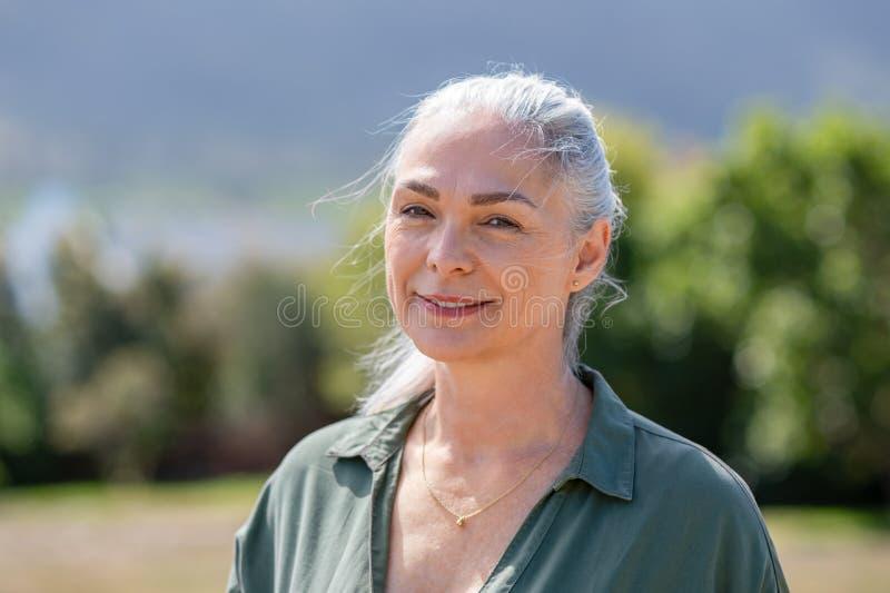 Mulher madura de sorriso que olha a câmera exterior imagem de stock royalty free
