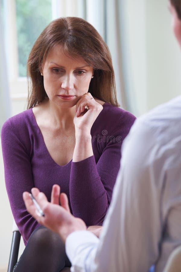 Mulher madura deprimida que fala ao conselheiro imagem de stock