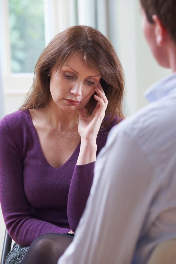Mulher madura deprimida que fala ao conselheiro foto de stock royalty free