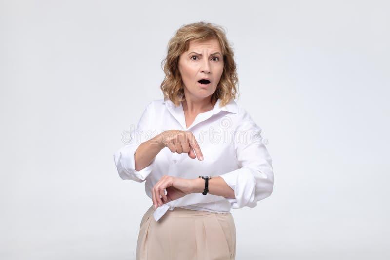 A mulher madura do chefe está irritada devido a seu colega de trabalho que está atrasado imagem de stock royalty free