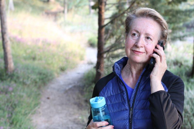 Mulher madura do turista que usa uma comunicação esperta do curso do parque da árvore do verde das férias de verão do sorriso do  foto de stock
