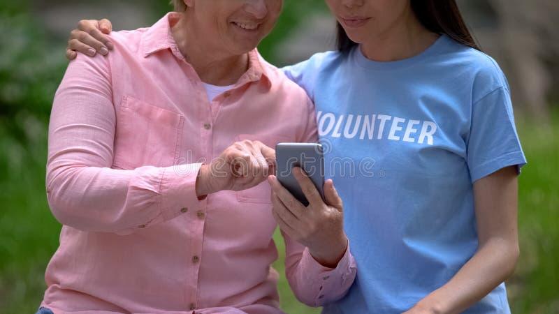 Mulher madura e jovem voluntária olhando fotos de smartphone juntos, assistência imagens de stock