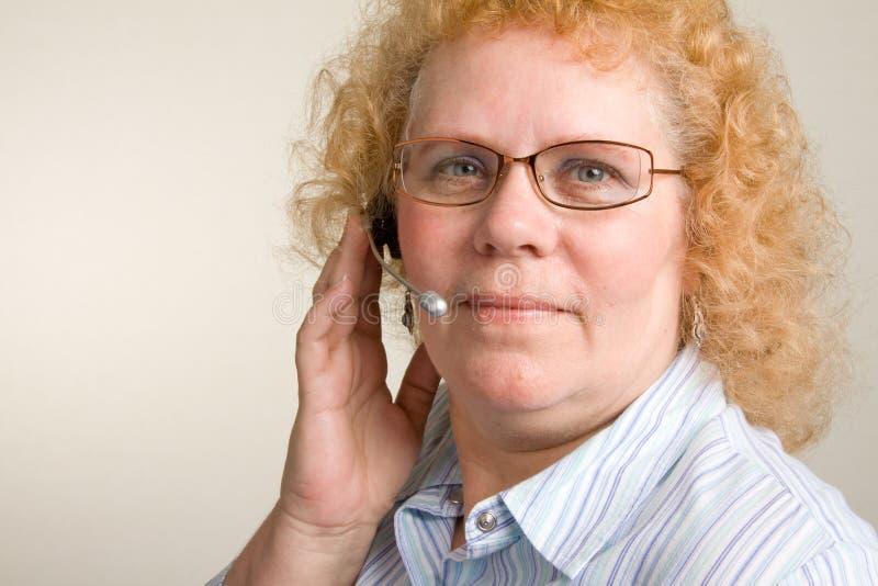 Mulher madura em auriculares do telefone foto de stock royalty free