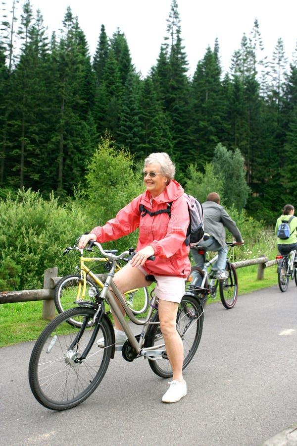 Mulher madura em sua bicicleta imagem de stock royalty free