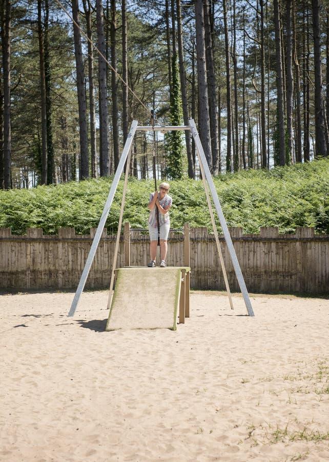 Mulher madura em um balanço da corda no parque fotografia de stock royalty free
