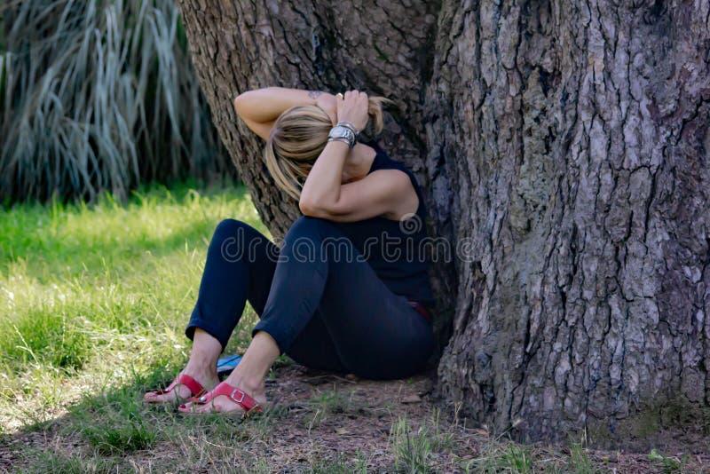 Mulher madura em uma inclinação de sorriso de assento do parque para trás em um log, louro com vidros e vestido no preto foto de stock