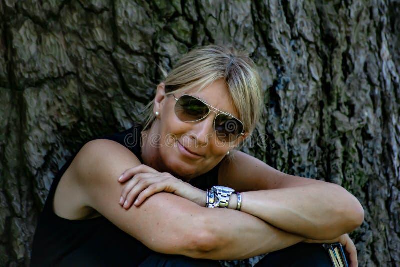 Mulher madura em uma inclinação de sorriso de assento do parque para trás em um log, louro com vidros e vestido no preto imagem de stock
