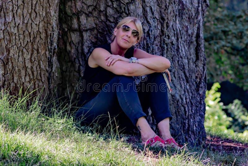 Mulher madura em uma inclinação de sorriso de assento do parque para trás em um log, louro com vidros e vestido no preto fotografia de stock royalty free
