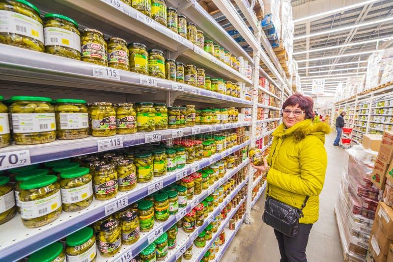 A mulher madura escolhe vegetais enlatados em um supermercado foto de stock royalty free