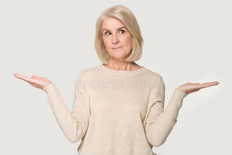 A mulher madura esticou as mãos que pensar faz a escolha no fundo branco imagem de stock royalty free