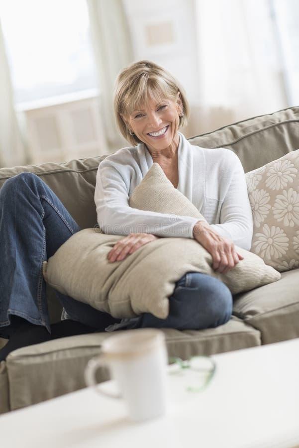 Mulher madura feliz com o coxim que senta-se no sofá imagens de stock royalty free