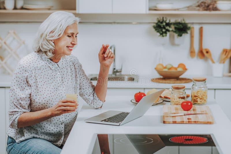 A mulher madura feliz está olhando o portátil durante o cozimento em casa fotografia de stock