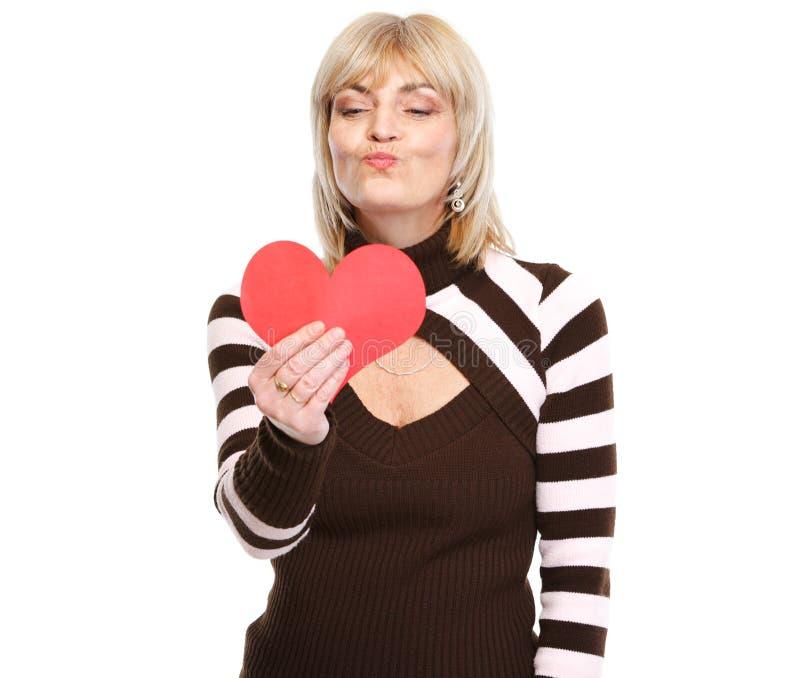 Mulher madura feliz que aprecia o cartão dado forma coração foto de stock