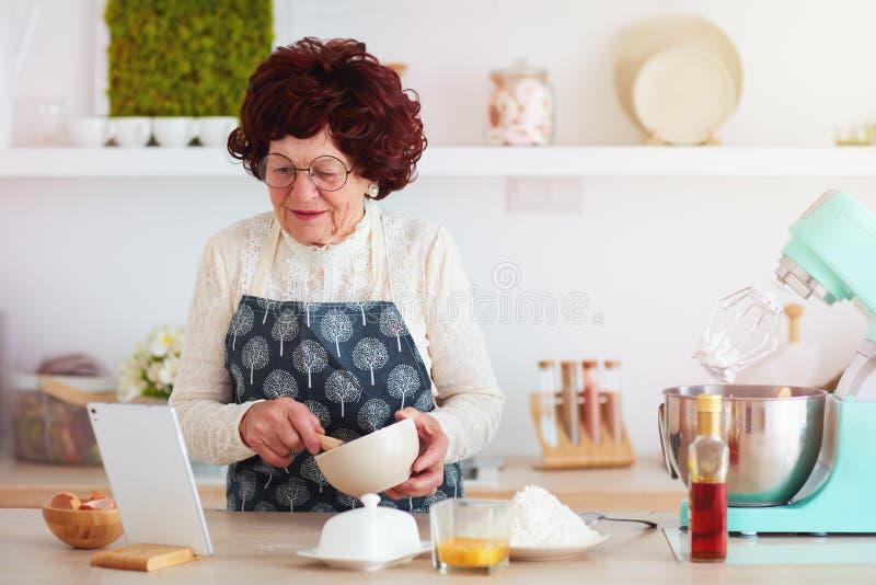 Mulher madura feliz que coze com a ajuda do Internet, receita de observa??o na tabuleta fotografia de stock