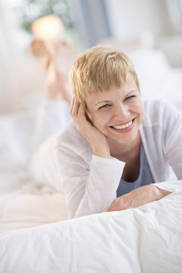Mulher madura feliz que encontra-se na cama imagens de stock