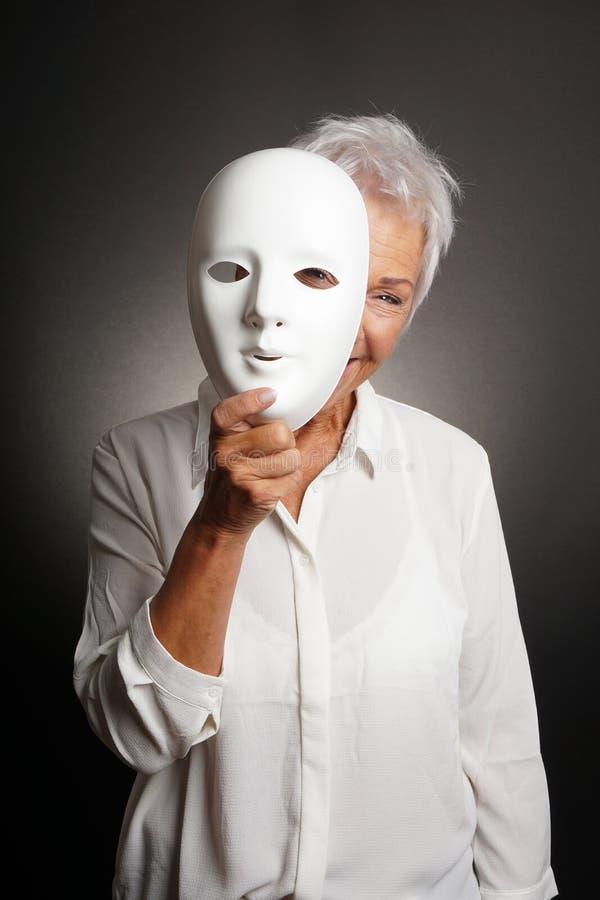 Mulher madura feliz que espreita da máscara de trás imagens de stock