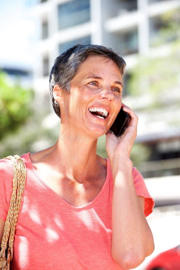Mulher madura feliz que fala no telefone celular fora fotografia de stock royalty free
