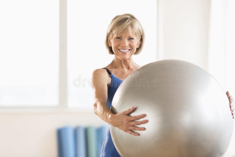 Mulher madura feliz que guarda a bola da ioga em casa imagem de stock