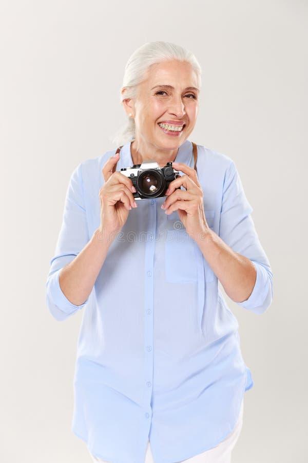 Mulher madura feliz que mantém a câmera retro isolada sobre o branco fotos de stock