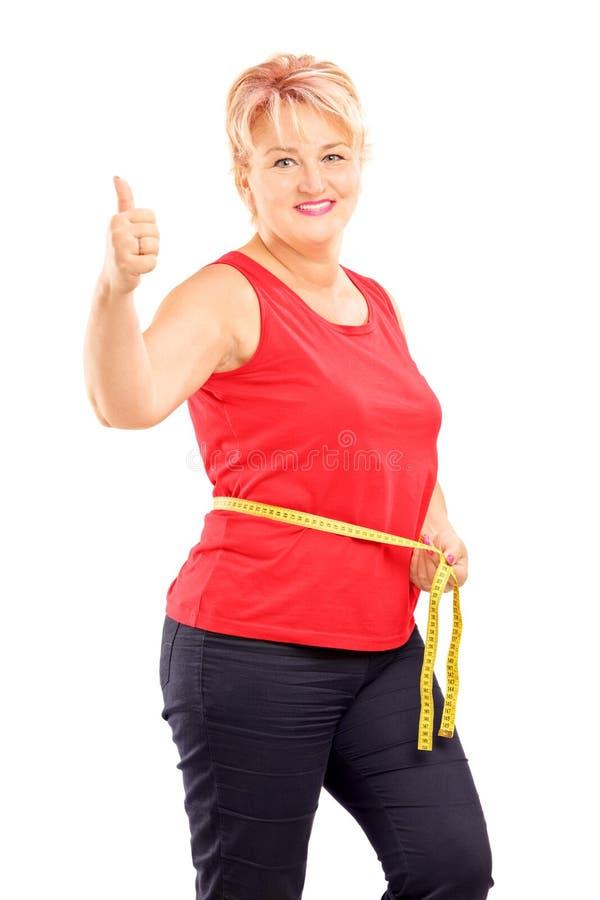 Mulher madura feliz que mede sua cintura após a dieta e que dá o thum imagens de stock