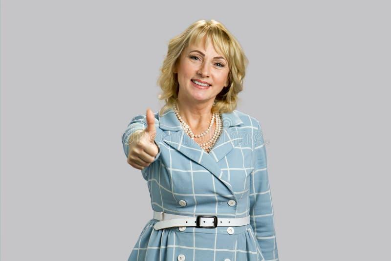 Mulher madura feliz que mostra o polegar acima imagens de stock