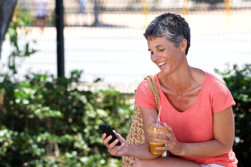 Mulher madura feliz que senta-se fora com bebida e que usa o telefone celular imagem de stock