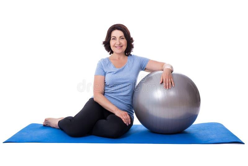 Mulher madura feliz que senta-se na esteira da ioga com o isolado da bola da aptidão foto de stock