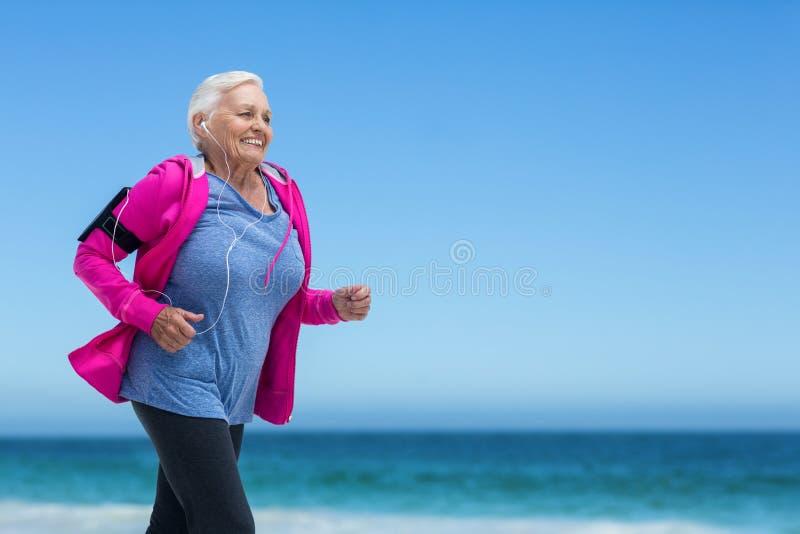 Mulher madura focalizada que corre e que escuta a música fotografia de stock royalty free