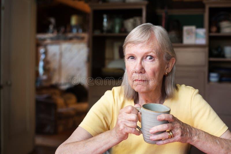 Mulher madura irritada que guarda o copo foto de stock