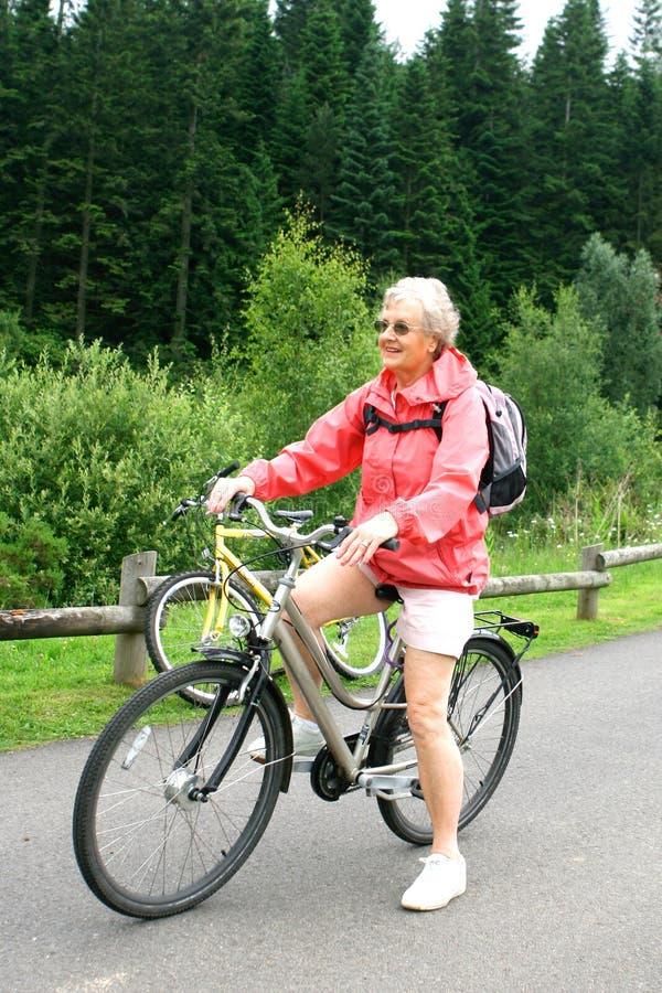 Mulher madura na bicicleta na floresta fotografia de stock royalty free