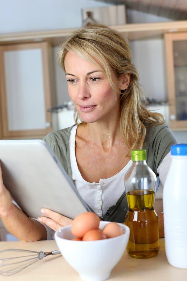 Mulher madura na cozinha que procura a receita imagens de stock