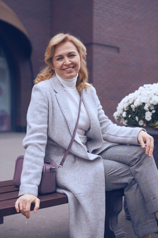 Mulher madura na moda que levanta na câmera ao sentar-se no outd do banco imagens de stock