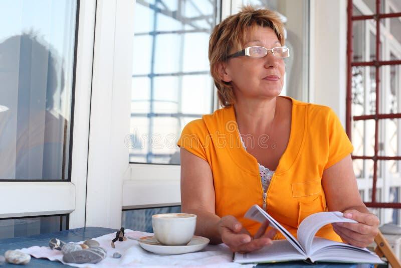 Mulher madura na tabela com livro e copo na manhã imagens de stock