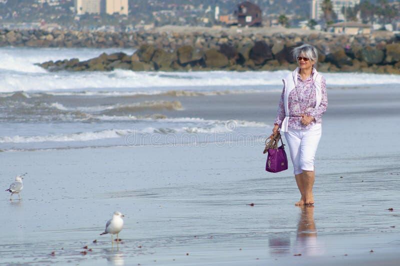 Mulher madura que anda na praia foto de stock