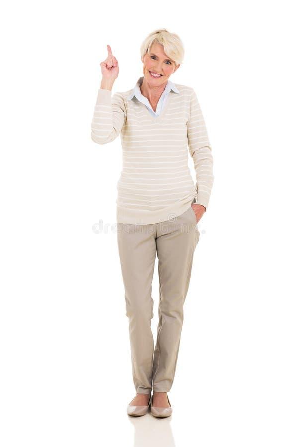 Mulher madura que aponta acima fotografia de stock
