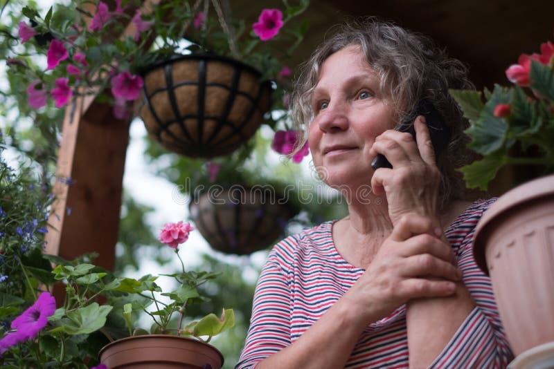 Mulher madura que chama o telefone e que olha flores imagem de stock