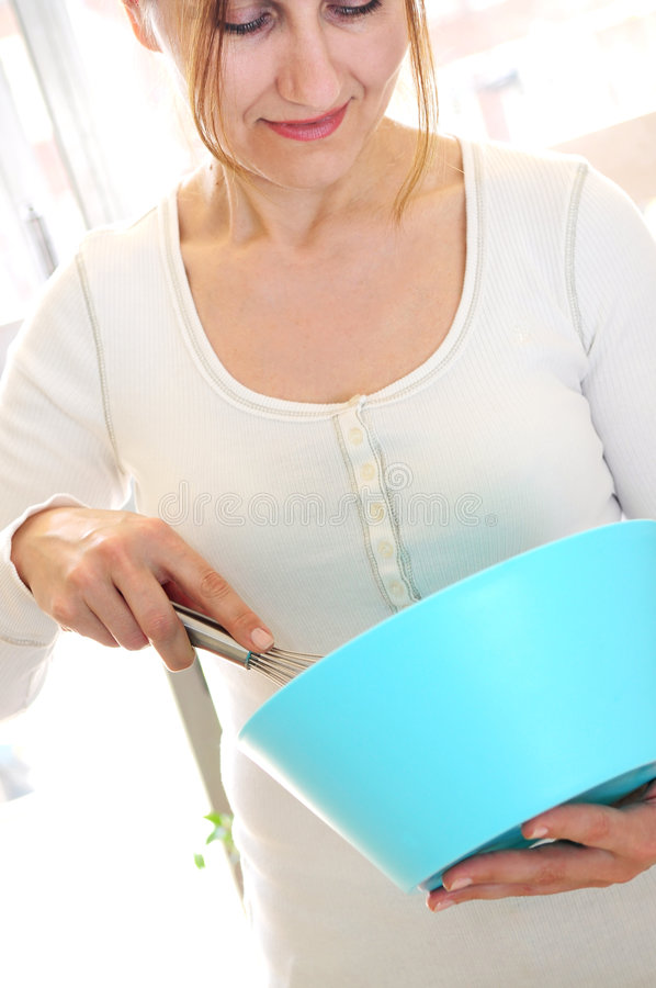 Mulher madura que cozinha em casa imagens de stock
