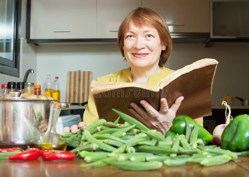 Mulher madura que cozinha o quiabo com livro de receitas mim imagem de stock