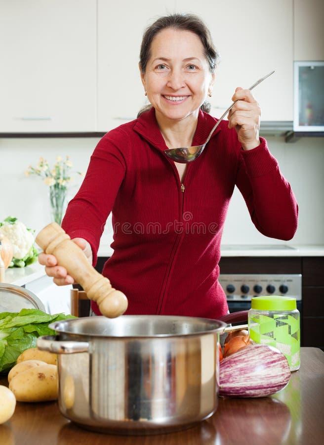 Mulher madura que cozinha a sopa em sua cozinha fotografia de stock